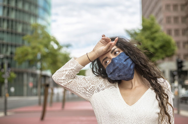 Close-up of woman wearing flu mask looking away standing outdoors