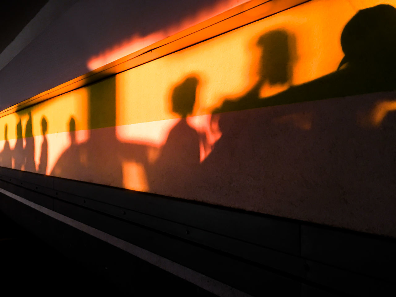 Shadow of people on illuminated wall at night
