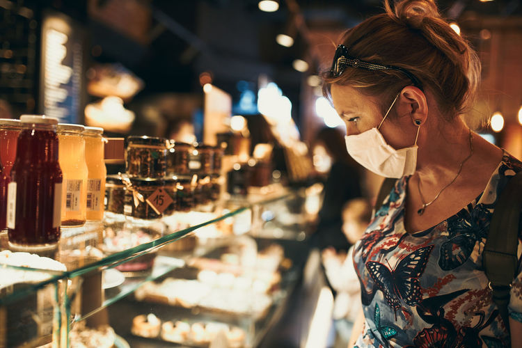Young woman shopping in grocery store in the evening, wearing the face mask to avoid virus infection