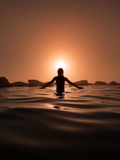 Silhouette woman standing in sea against sky during sunset