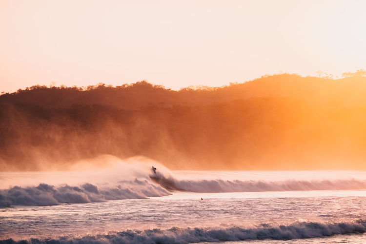 Surfer Surfers Paradise Beauty In Nature Day Flowing Water Idyllic Motion Nature No People Non-urban Scene Orange Color Outdoors Power In Nature Scenics - Nature Sea Sky Sunset Tranquil Scene Tranquility Water Waterfront Wave