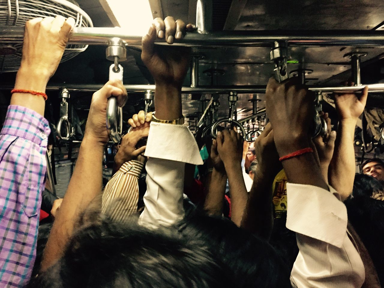 Crowd holding handle in train