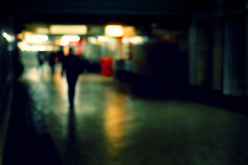 Defocused image of people walking in illuminated city at night