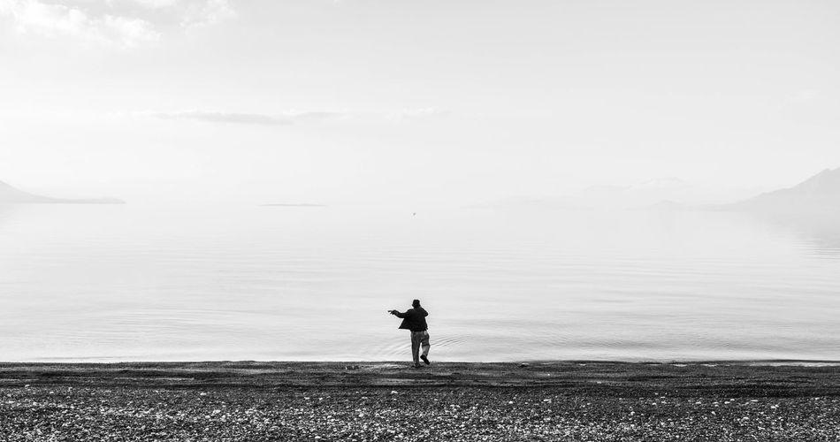 Full Length Of Man Throwing Rock In Sea Against Sky