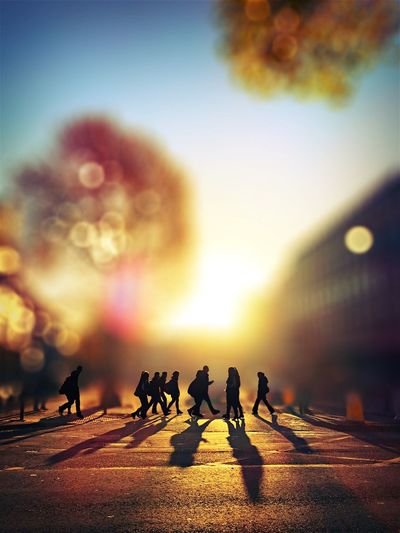 Tilt-Shift Image Of Silhouette People Walking On City Street During Sunset