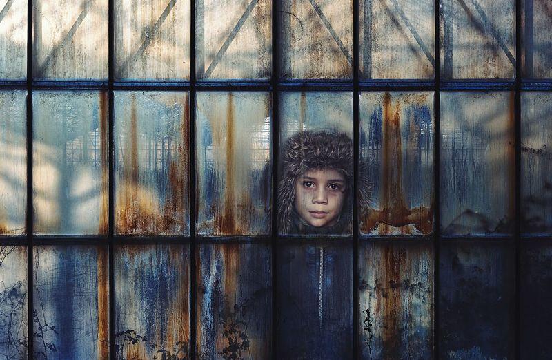 Portrait Of Boy Seen Through Damaged Window Of Building