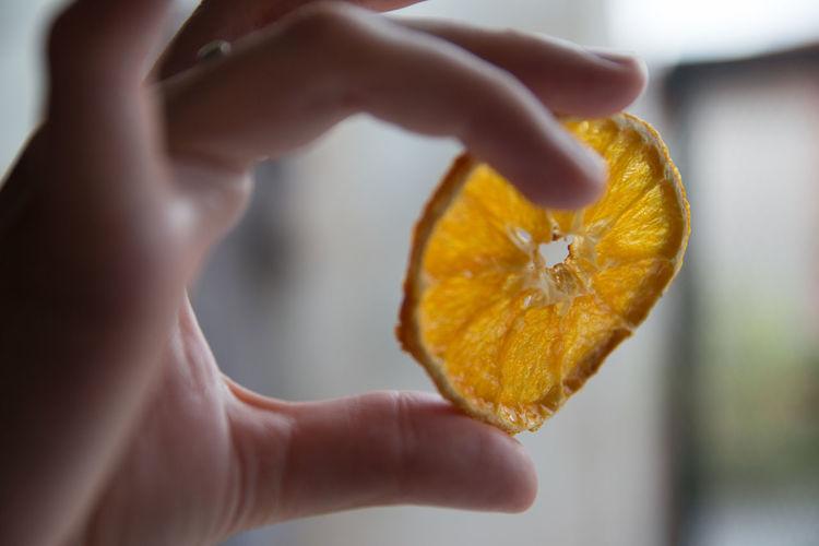 Close-up of hand holding orange slice
