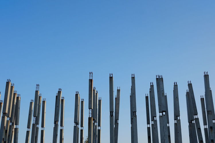 Low angle view of wooden posts against clear blue sky
