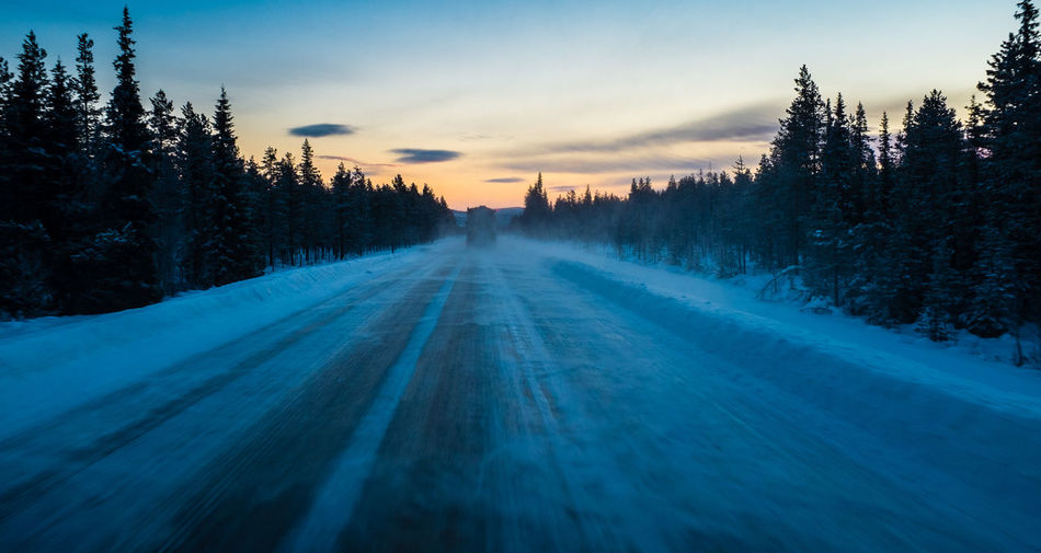 Snow covered road against sky at sunset