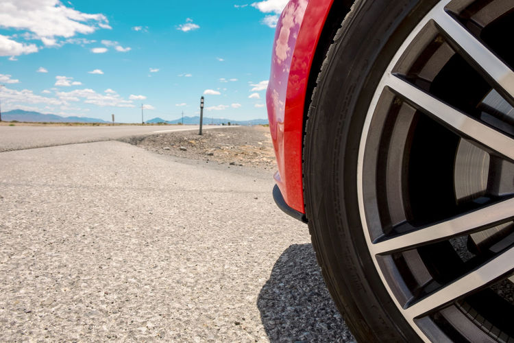 Close-up of tire of red sports car on road