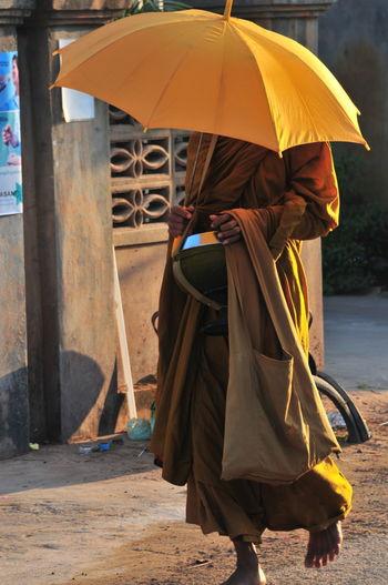 Buddhist Monks Cambodia Casual Clothing Front View Full Length Fun Hobbies Holding Leisure Activity Lifestyles Men Monochrome Real People Rear View Recreational Pursuit Standing Three Quarter Length Vacations Walking Women