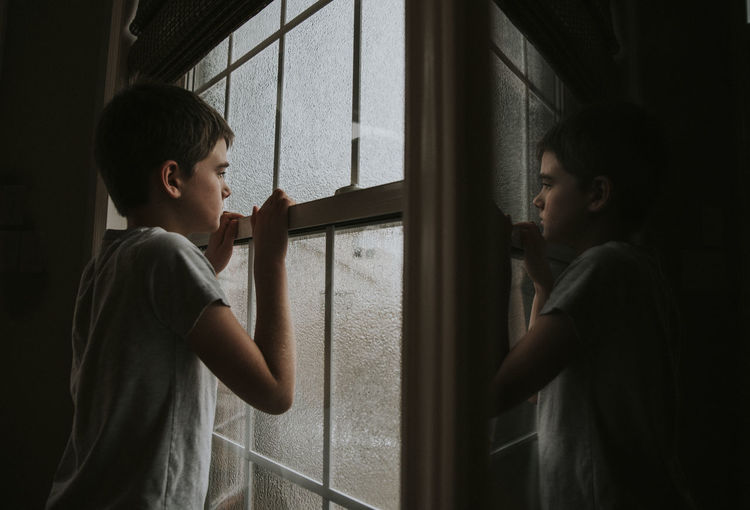 Side view of girl standing by window