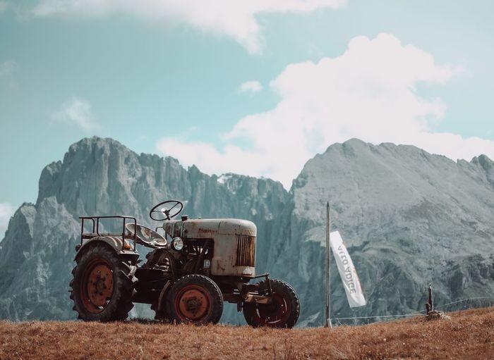 Vintage car on field against mountain range