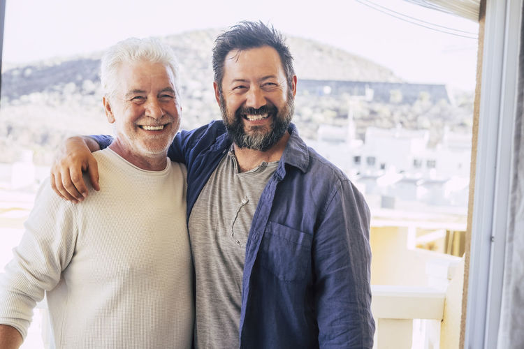 Portrait Of Smiling Father And Son Standing Against Window