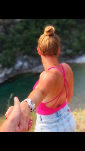 Rear view of woman holding hands in water