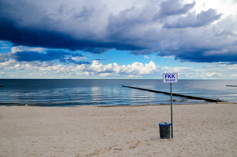 Signboard by garbage can at beach with baltic sea against cloudy sky