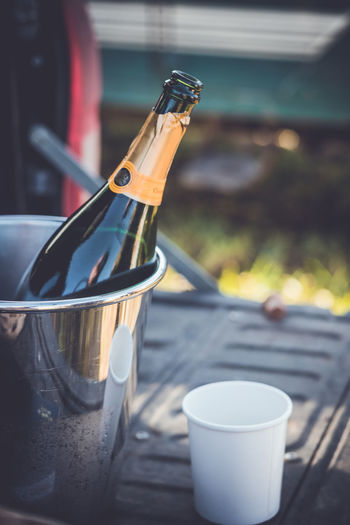 An ice bucket, a bottle of champagne, paper cup and champagne glasses on the back of a 4x4. 4x4 Champagne Paper Cup Rural Bottle Champagne Bottle Champagne Flute Close-up Day Drink Focus On Foreground Food And Drink Freshness Hamper Ice Bucket No People Shooting Table