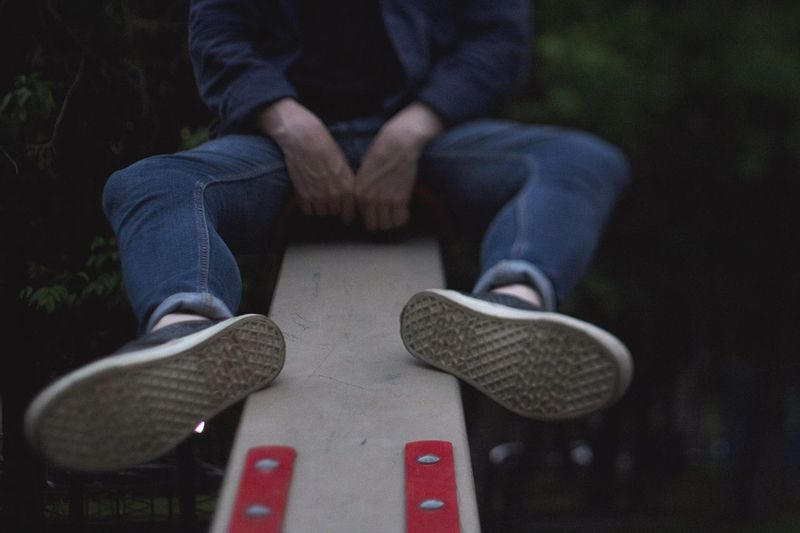 Close-up of man sitting on seesaw at park