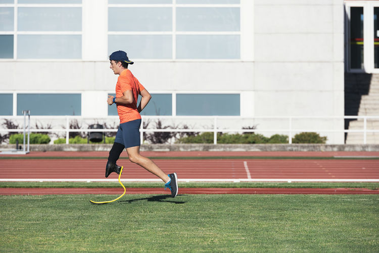 Side view of athlete with prosthetic leg running on grass at track