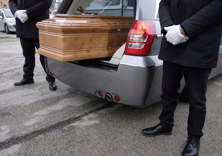Low section of men standing amidst casket in van on road