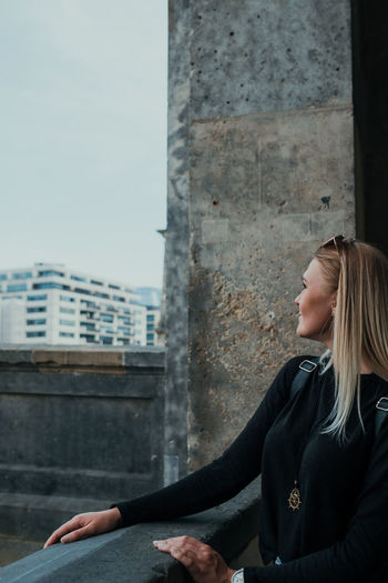Side view of young woman sitting against building in city