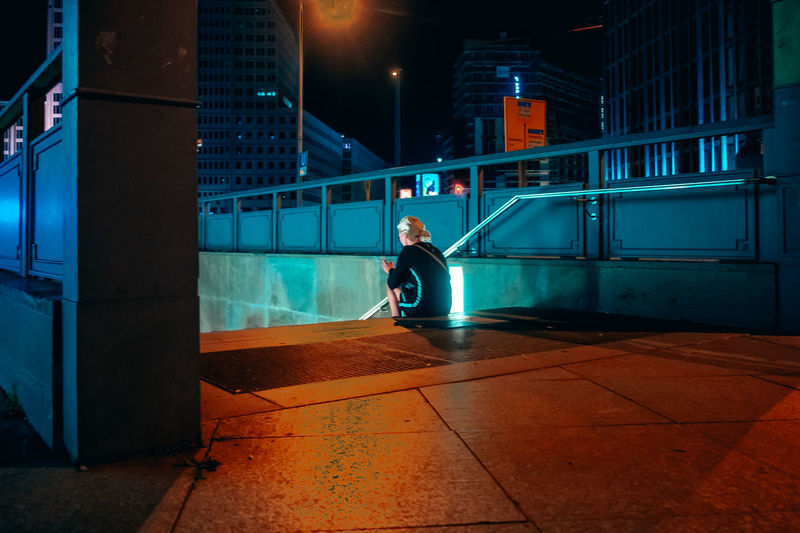 Side view of man sitting on footpath at night