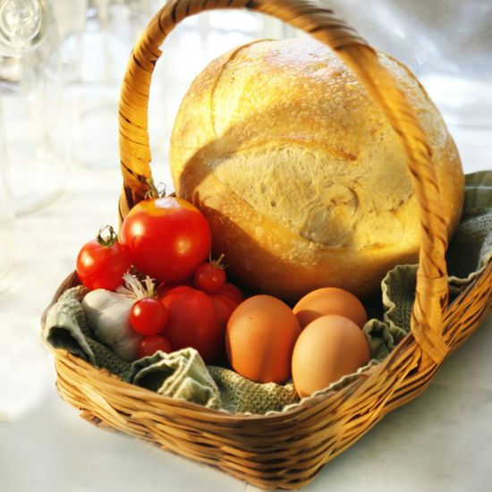 High angle view of eggs with tomatoes and bread in wicker basket