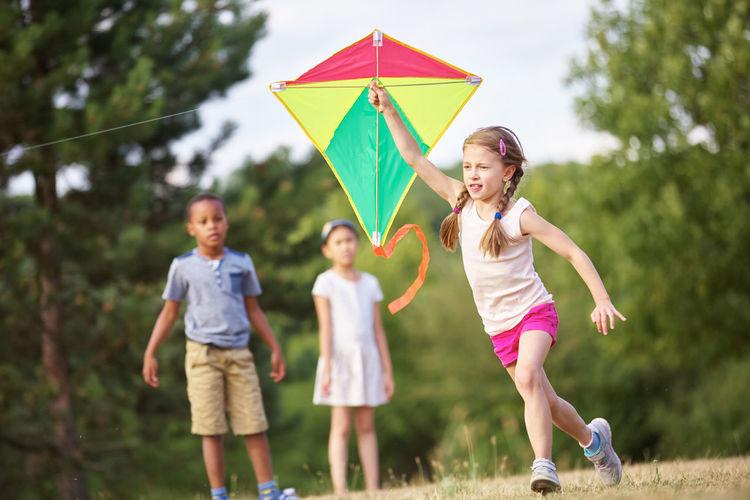 Girl holding kite while running at park