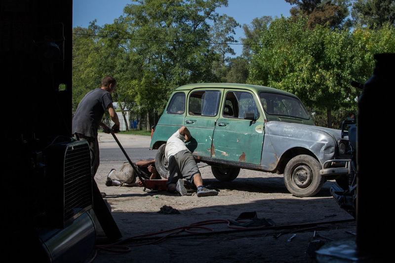 Rear view of a man repairing car