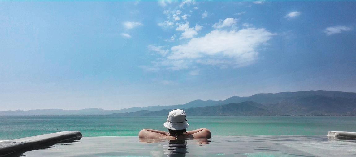 Woman relaxing in swimming pool against sea