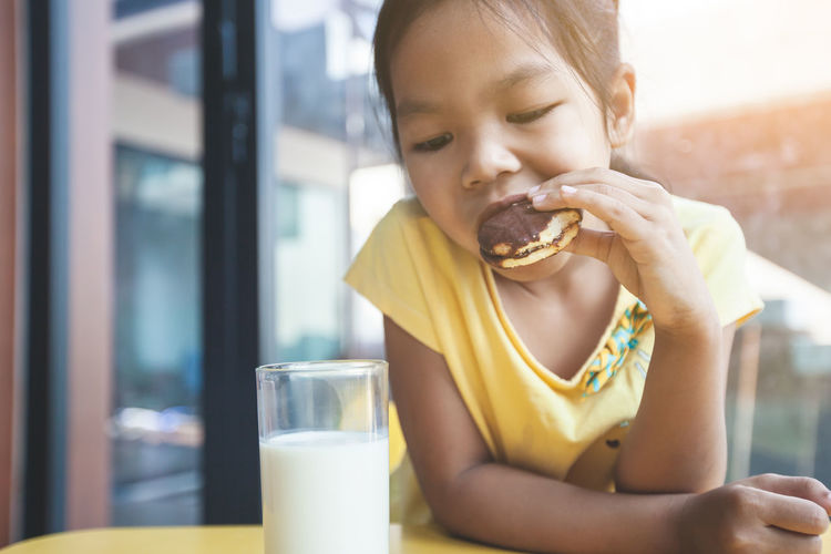 Close-up of girl eating food on table at home