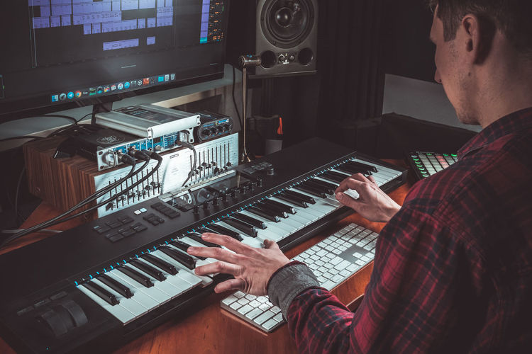 Male musician playing midi keyboard synthesizer in recording studio, focus on hands. Mens arms plays solo of music or new melody. Close-up Music Musical Equipment Musical Instrument Real People Indoors  Human Hand Keyboard Piano MIDI Keyboard Music Hand Hands