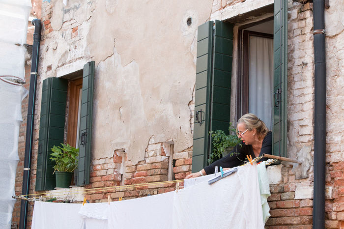 An unidentified lady hanging out clothes outside her house. An Unidentified Lad Architecture Balcony Day Flower Pot Hanging Clothes Potted Plant Residential Building Stone Material Window