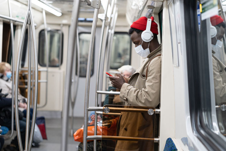 Side view of man wearing mask using mobile phone in train