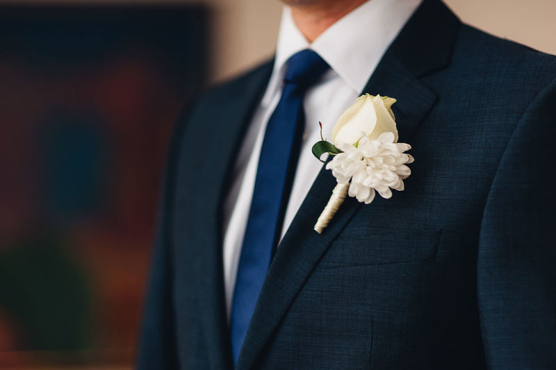 Midsection of man holding flower in bloom