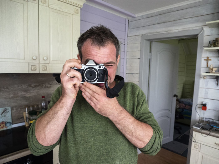 Man Photographing From Camera In Kitchen At Home
