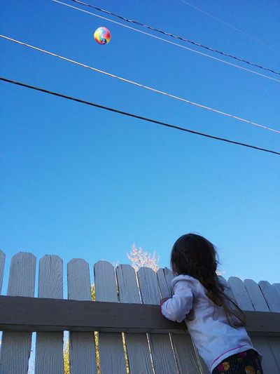 Low Angle View Of Girl Standing By Fence While Looking At Ball