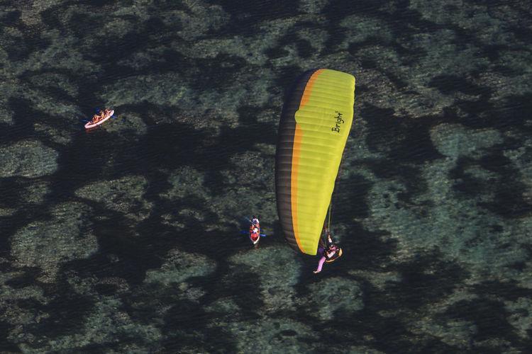 Person paragliding against sea