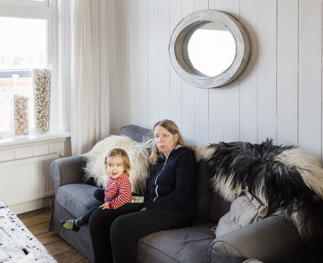 Woman Sitting With Granddaughter On Sofa At Home