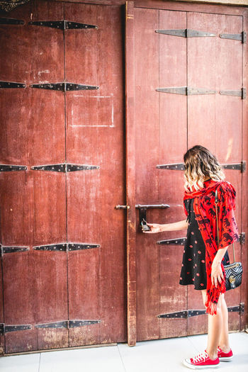 Side view of woman standing against door