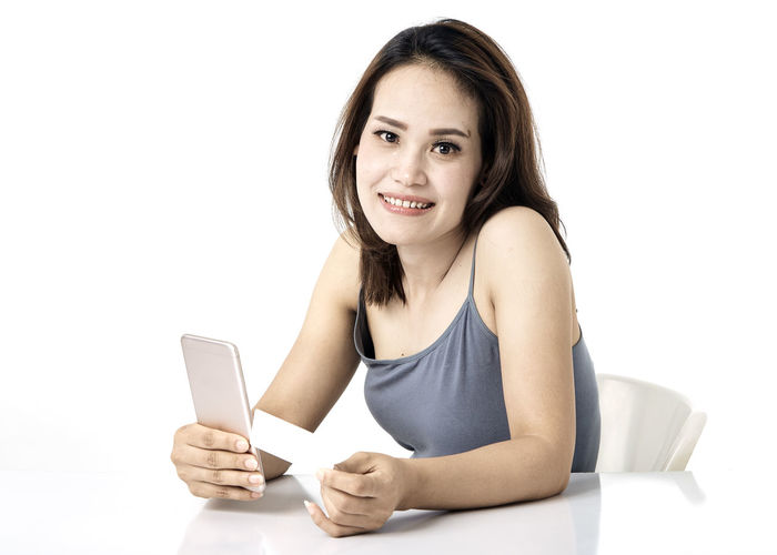 Thai Studio Shot 30-34 Years Shopping Online  Young Female Happy Asian  Laptop Beautiful Internet Attractive Smile person Computer People Portrait Holding Phone Beauty Mobile Pretty Technology Payment Adult Using Lifestyle Cheerful Purchase Business Wireless Lady Chinese Fashion Looking Smartphone Japanese  Korean Credit Card Empty Text Copy Space Communication White Background Looking At Camera Connection Front View Indoors  Wireless Technology Smiling One Person Young Adult Young Women Cut Out Casual Clothing Lifestyles Portable Information Device Hair Beautiful Woman Hairstyle