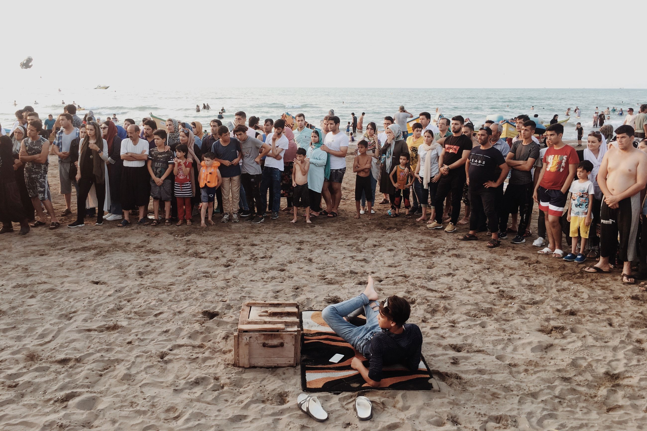 crowd, large group of people, group of people, land, real people, men, sand, beach, leisure activity, adult, casual clothing, women, sea, day, trip, holiday, sitting, full length, sky, outdoors