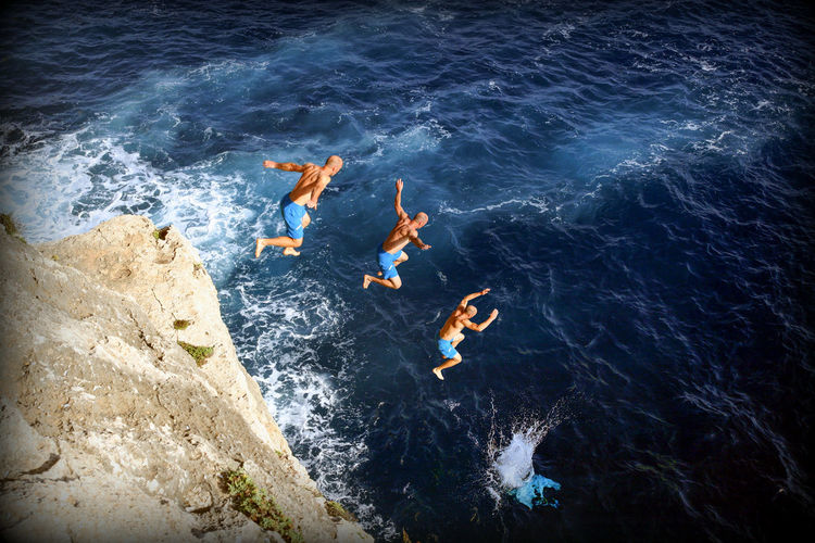 High Angle View Of Man Jumping In Sea