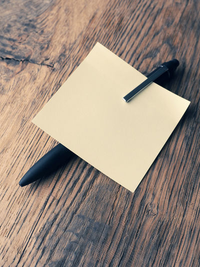 Sticky note with a pen on a wooden office table Wood - Material Paper Indoors  Table No People High Angle View Still Life Close-up Blank Wood Pen Writing Instrument Copy Space Note Pad Office Note Office Supply Empty Textured  Document Reminder Sticky Notes Ofiice Business Message