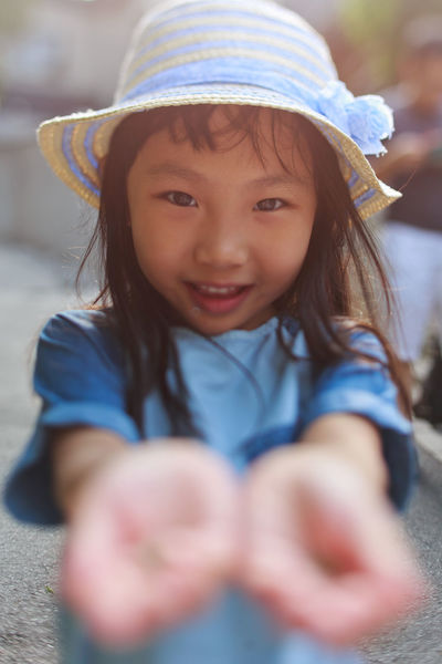 Cute little asian girl showing something on the palm of her hand Childhood Portrait Females Hat Child Girls Front View One Person Women Cute Innocence Real People Looking At Camera Smiling Clothing Leisure Activity Selective Focus Happiness Emotion Hairstyle Palm Tree Asian Girl