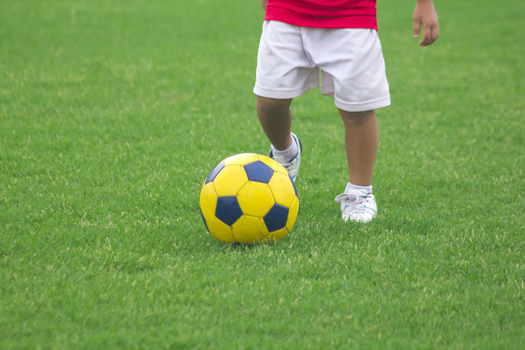 Low section of boy playing soccer on field