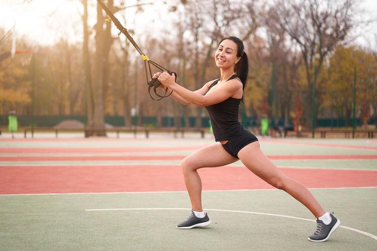 Full length of woman exercising ta sports court