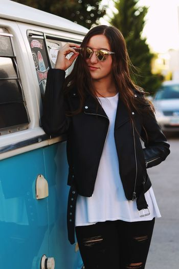 Young woman wearing sunglasses by van on street