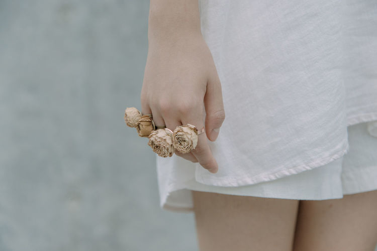 Midsection Of Young Woman Wearing Rose Shape Rings Against Wall