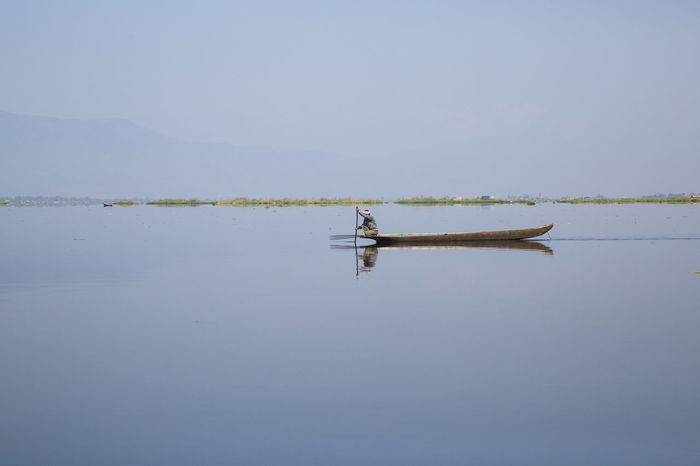 Man on a boat on Loktak Lake (Manipur, India) ASIA India Loktak Manipur North-Eastern India Tranquility Travel Beauty In Nature Boat Calm Water Clear Sky Day Lake Nature Naturelovers One Man Only One Person Outdoors People Sky Travel Destination Travelindia Travelphotography Water Waterfront